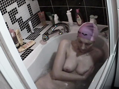 Skinny mature looker with large saggy tits washes her tight asshole